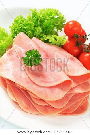 Stacked slices of ham salami with parsley and cherry tomatoes on a white tray