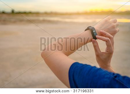 Young Asian Woman Touching Smart Band After Running In The Morning. Wearable Computer. Heart Rate Mo
