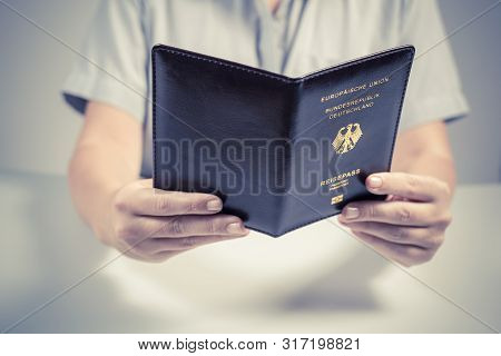 Immigration and passport control at the airport. woman border control officer with Deutsch passport of German citizen. Concept poster