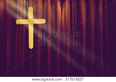 Yellow Wood Cross On Dark Brown Curtain Background In Small Church With Ray Of Light