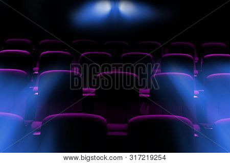 Empty Movie Theater With Purple Seats With Flare Light Rays From Projector