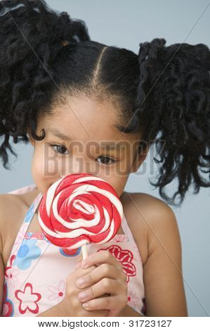 Portrait of Asian girl with ponytails holding sucker in front of face