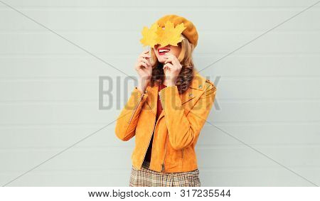 Autumn Mood! Happy Smiling Woman Holding In Her Hands Yellow Maple Leaves Hiding Her Eyes Over Gray