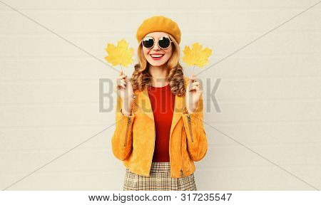 Autumn Mood! Stylish Happy Smiling Woman With Yellow Maple Leaves In French Beret Over Gray Wall Bac