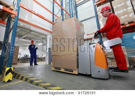 Goods delivery - two workers  with forklift loader working in storehouse