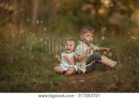 Two Beautiful Happy Little Children With Flowers. The Boy Blows On A Dandelion. The Girl Smiles And