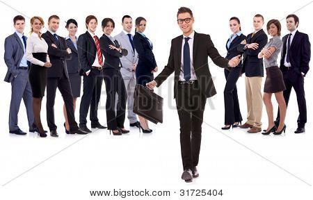 Business leader walking with briefcase in his hand, welcoming you to the team , isolated on white . young business man with suitcase walking towards the camera with a large business team behind him