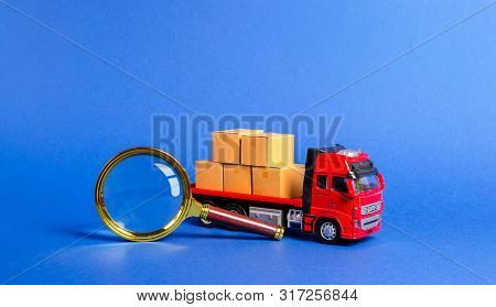 Red Truck Loaded With Boxes And A Magnifying Glass. Search For A Carrier And Routes For Transportati