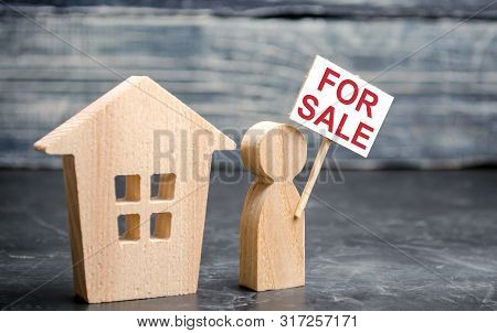 House And Person With A Sign For Sale. Sale Of Real Estate By The Owner. Attracting Customer Attenti
