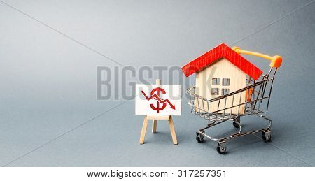 House In The Shopping Cart And A Stand With Red Chart Arrow Down. The Fall Of The Real Estate Market