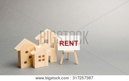 Three Figures Of Houses And An Easel With The Word Rent. The Concept Of Temporary Rental Housing And