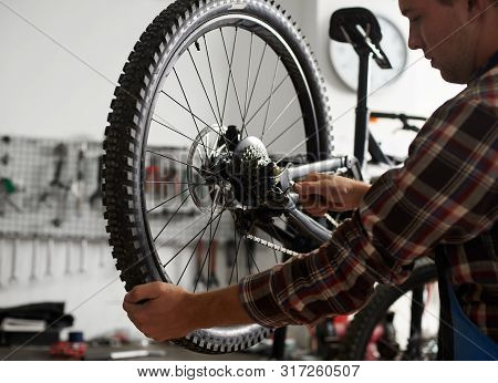 Cropped Shot Of Male Mechanic Working In Bicycle Repair Shop, Repairman Fixing Bike Using Special To