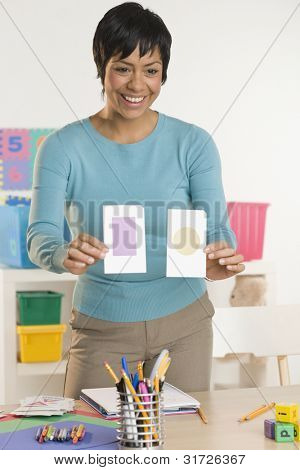 Female teacher holding up flash cards
