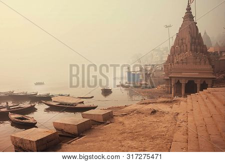 Varanasi, India: Sunrise In Misty Indian City With Monumental Temples And Riverboats In Ganga River