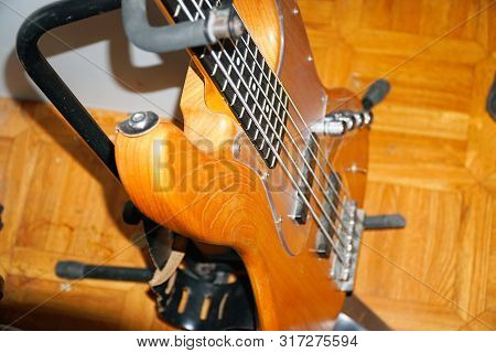 Bass Guitar With Wooden Body On Stand