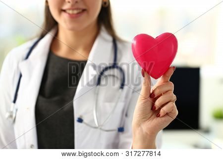 Beautiful Smiling Blond Female Doctor Hold In Arms Red Toy Heart Closeup. Cardio Therapeutist Studen