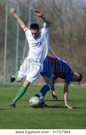 KAPOSVAR, HUNGARY - MARCH 17: Milan Szolomayer (white) in action at the Hungarian National Championship under 18 game between Kaposvar (white) and Videoton (blue), March 17, 2012 in Kaposvar, Hungary.