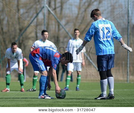 KAPOSVAR, HUNGARY - MARCH 17: Edvard Rusak (12) in action at the Hungarian National Championship under 18 game between Kaposvar (white) and Videoton (blue), March 17, 2012 in Kaposvar, Hungary.