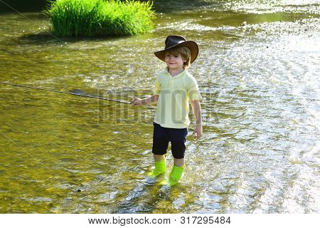 Cute Little Boy Fishing On Pond. Young Man Fly Fishing. Photo Of Little Boy Fishing. Boy In Yellow S