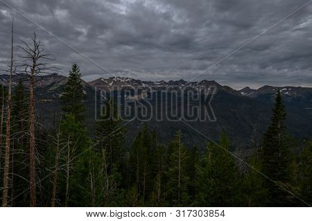 Rocky Mountains National Park view with trees in foreground at sunrise