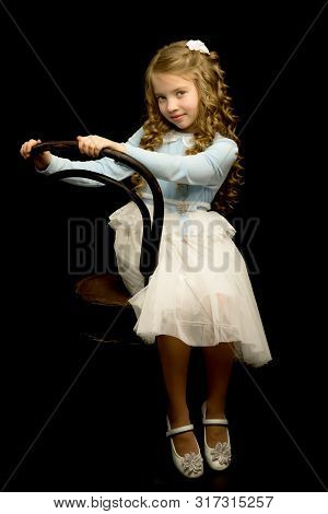 Portrait Of A Beautiful Little Girl Sitting On An Old Viennese Chair, Studio On A Black Background.