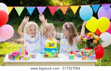 Children Blow Candles On Birthday Cake. Kids Party