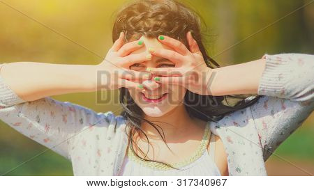 Girl Put Her Hands And Fingers To His Forehead To Shield His Eyes From The Sun, Looks Up And Happy.