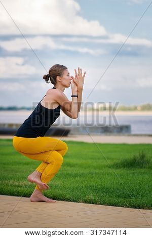 Young Beautiful Woman Practicing Yoga With Cloudy Sky In The Background. Wellness Concept. Calmness