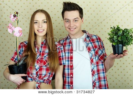 Happy couple with domestic flowers looking at camera