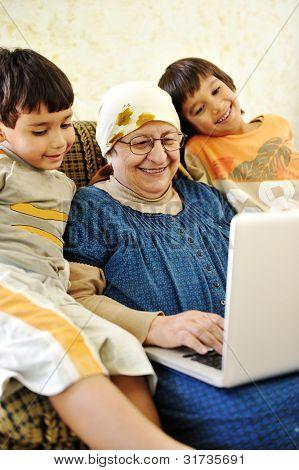 Elderly woman working on laptop in  house