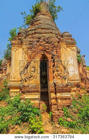 Ruined Statue At The Entrance Of The Ancient Stupas At Indein Overgrown With Plants, Inle Lake Myanm