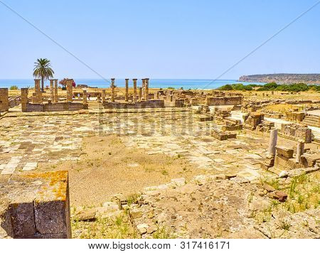 Remains Of The Forum Square With The Basilica In The Background. Baelo Claudia Archaeological Site.