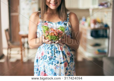 Front View Of Happy Pregnant Female Standing In Kitchen, Keeping Plate With Vegetables And Smiling.