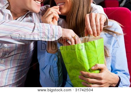 Couple in cinema theater watching a movie, they eating popcorn, close-up
