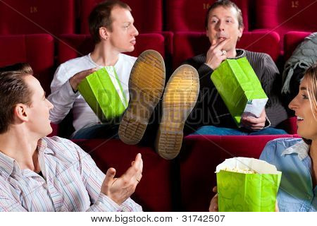 Five people - amongst them a couple - in cinema theater watching a movie, they eating popcorn