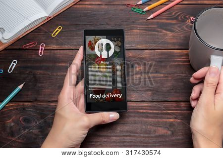 The Woman Uses The Application On The Mobile To Order Food Delivery. Online Delivery