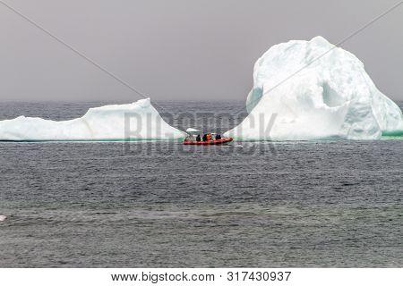 Iceberg Floating Off Newfoundland Coast With Tourist Boat