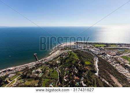 Aerial of view of hilltop homes, Malibu Pier, and Surfrider beach north of Los Angeles in Southern California.