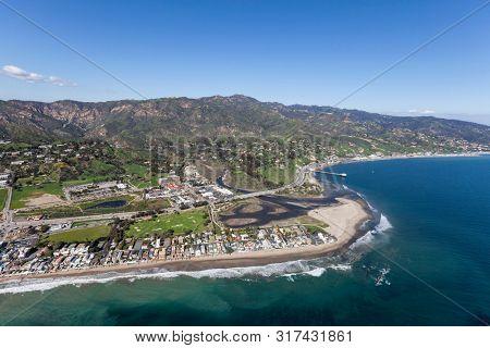 Aerial view towards shoreline homes, Malibu Lagoon and Surfrider Beach in scenic Malibu, California.
