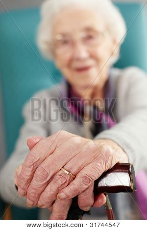 Senior Woman Relaxing In Chair Holding Walking Stick