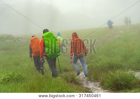 Travelers With Backpacks And Professional Tourist Equipment Climbing Carpathian Mountains. Hard Hiki