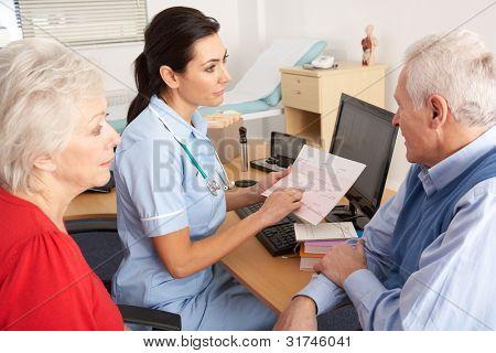 British nurse talking to senior couple