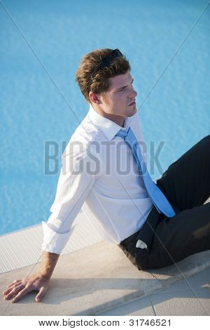Elegant man relaxing by pool, could be a businessman or  a man  relaxing during a cerimony