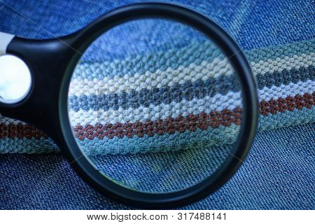 Black Magnifier Enlarges Striped Colored Belt On Blue Cotton Fabric