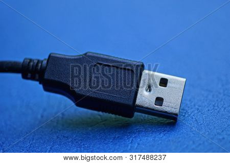 Black Long Usb Cord With Plug On A Blue Table