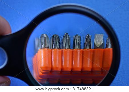 Magnifier Enlarges A Set Of Screwdriver Bits In A Red Plastic Box