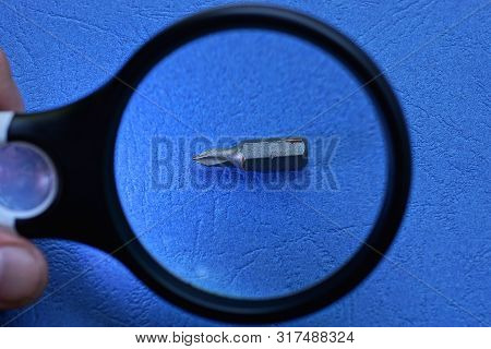 Magnifier Enlarges One Gray Metal Screwdriver Bit On Blue Table