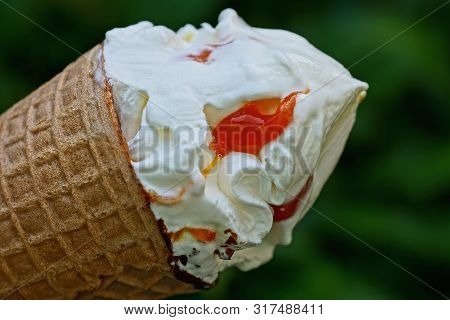 White Ice Cream With Red Jam In A Waffle Cup On A Green Background