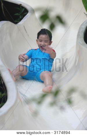 Boy Sliding At The Pool