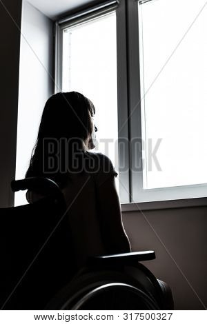 Invalid or disabled young woman person sitting wheelchair indoor looking window daylight bright sky